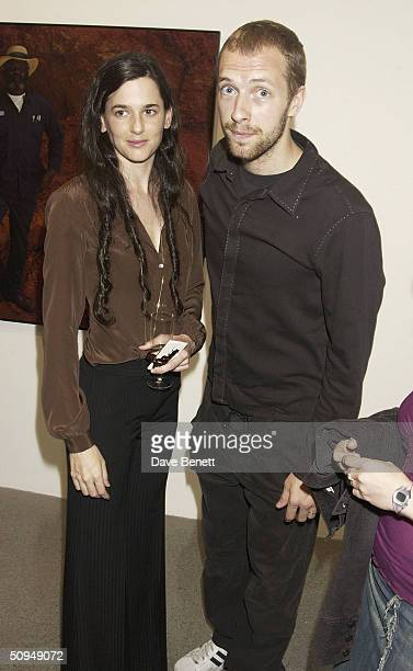 Coldplay singer Chris Martin and photogrpaher Taryn Simon attend an exhibit known as The Innocents at the Gogasian Gallery June 10 2004 in London...