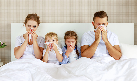 colds and viral diseases. family with runny nose and fever in bed 1182706731