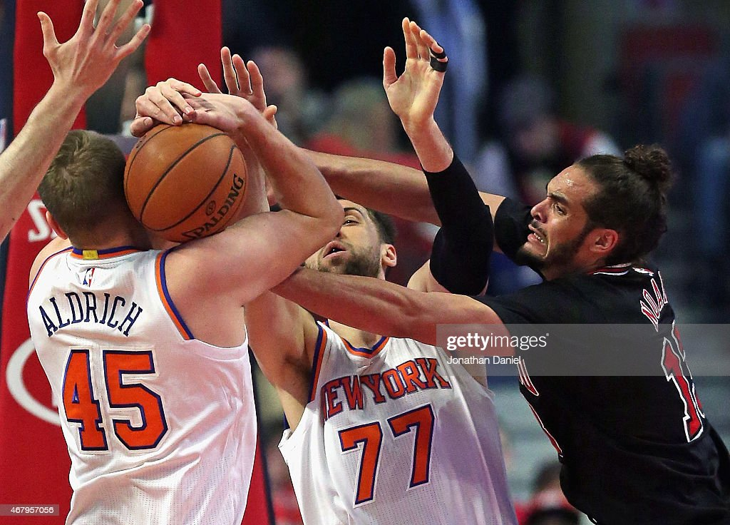 Cole Aldrich #45 of the New York Knicks fights to keep the ball from teammate Andrea Bargnani #77 and Joakim Noah #13 of the Chicago Bulls at the United Center on March 28, 2015 in Chicago, Illinois.