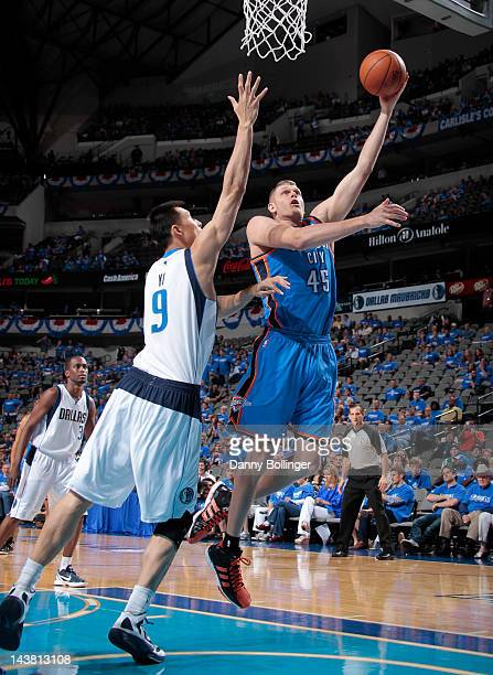 Cole Aldrich of the Oklahoma City Thunder goes in for the layup against Yi Jianlian of the Dallas Mavericks in Game Three of the Western Conference...