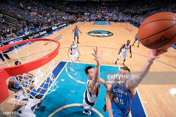 Cole Aldrich of the Oklahoma City Thunder puts up the layup against Yi Jianlian of the Dallas Mavericks in Game Three of the Western Conference...