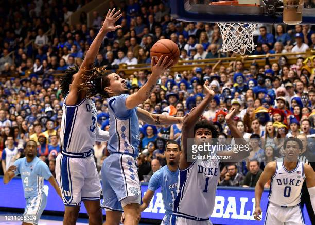 Cole Anthony of the North Carolina Tar Heels drives between Tre Jones and Vernon Carey Jr. #1 of the Duke Blue Devils during the second half of their...
