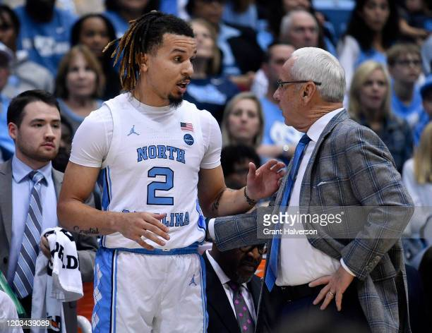 Cole Anthony talks with head coach Roy Williams of the North Carolina Tar Heels during the first half of their game against the Boston College...