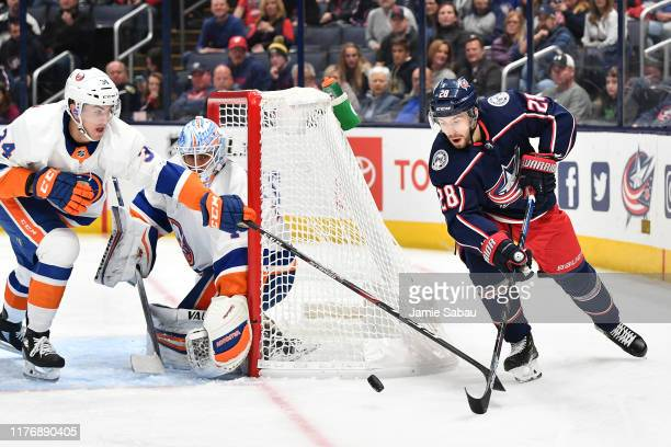 Cole Bardreau of the New York Islanders and Oliver Bjorkstrand of the Columbus Blue Jackets reach for a loose puck as goaltender Thomas Greiss of the...