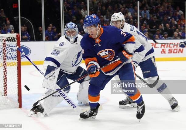 Cole Bardreau of the New York Islanders attempts to corral the puck during the second period against Andrei Vasilevskiy of the Tampa Bay Lightning at...
