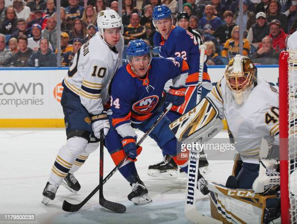 Cole Bardreau of the New York Islanders is defended by Henri Jokiharju and Carter Hutton of the Buffalo Sabres during an NHL game on November 2 2019...