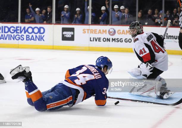 Cole Bardreau of the New York Islanders is tripped while shooting against Craig Anderson of the Ottawa Senators during their game at Barclays Center...