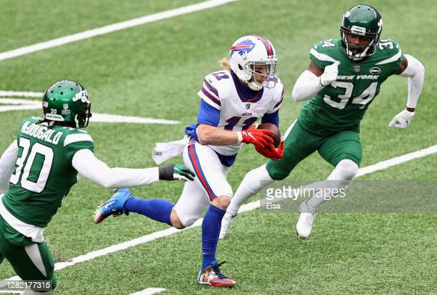 Cole Beasley of the Buffalo Bills runs with the ball as Bradley McDougald and Brian Poole of the New York Jets pursue Beasley in the second quarter...