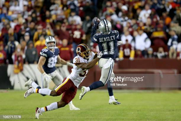Cole Beasley of the Dallas Cowboys catches a pass over Fabian Moreau of the Washington Redskins during the second half at FedExField on October 21...