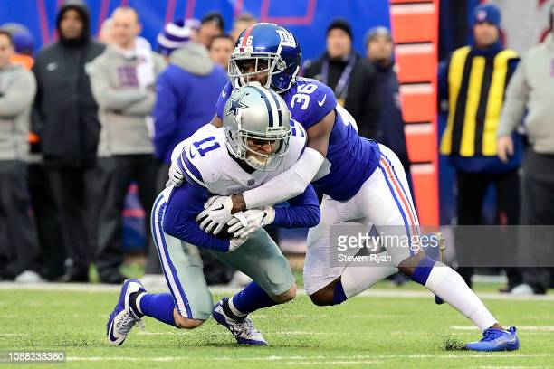 Cole Beasley of the Dallas Cowboys converts on fourth down with a reception as he is tackled by Sean Chandler of the New York Giants during the third...