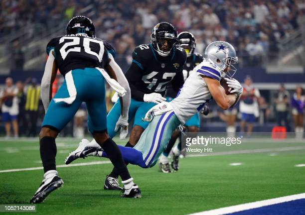 Cole Beasley of the Dallas Cowboys dives between Jalen Ramsey and Barry Church of the Jacksonville Jaguars for a touchdown in the second quarter of a...