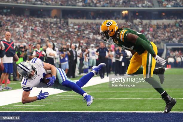 Cole Beasley of the Dallas Cowboys dives into the end zone for a touchdown ahead of Davon House of the Green Bay Packers at ATT Stadium on October 8...