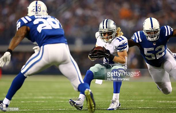 Cole Beasley of the Dallas Cowboys eludes D'Qwell Jackson of the Indianapolis Colts and Mike Adams of the Indianapolis Colts to score a touchdown in...