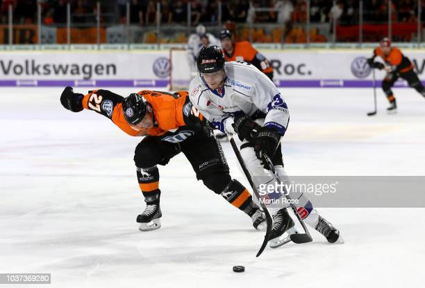 Cole Cassels of Wolfsburg and Stefan Loibl of Straubing battle for the puck during the DEL match between Grizzlys Wolfsburg and Straubing Tigers at...