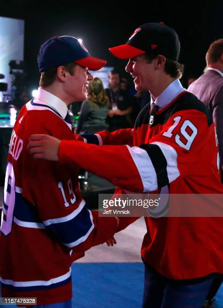Cole Caufield fifteenth overall pick of the Montreal Canadiens and Jack Hughes first overall pick of the New Jersey Devils congratulate one another...