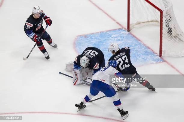Cole CAUFIELD, goaltender Spencer Knight and Ryan Johnson of the United States defend against Roman Faith of Slovakia during the 2021 IIHF World...