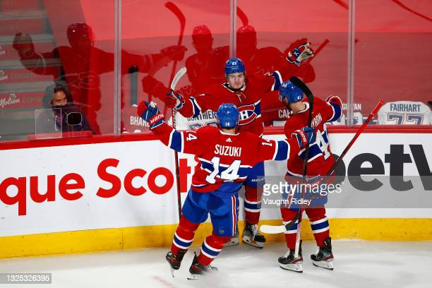 Cole Caufield of the Montreal Canadiens celebrates with Nick Suzuki and Paul Byron after scoring a goal against Robin Lehner of the Vegas Golden...