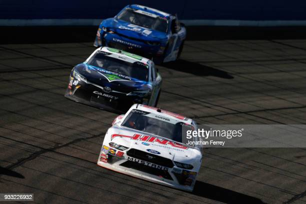 Cole Custer driver of the Haas Automation Ford leads Christopher Bell driver of the GameStop/Turtle Beach Toyota and Elliott Sadler driver of the...