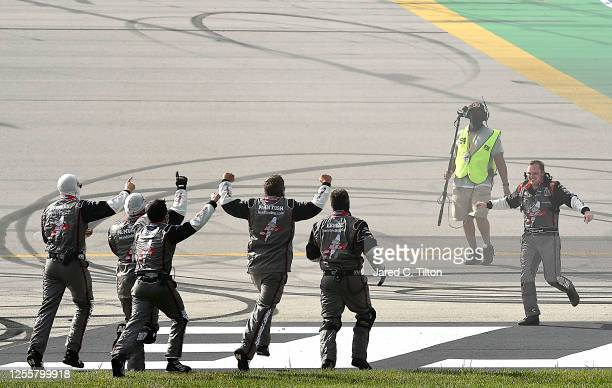 Cole Custer driver of the HaasToolingcom Ford and crew celebrate after winning the NASCAR Cup Series Quaker State 400 Presented by Walmart at...