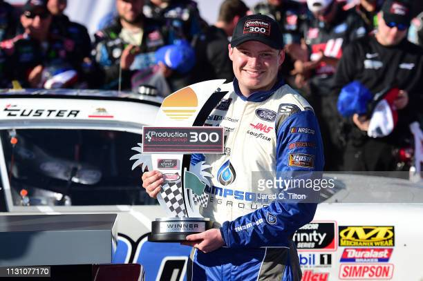 Cole Custer driver of the Thompson Pipe/Haas CNC Ford poses with the trophy in Victory Lane after winning the NASCAR Xfinity Series Production...