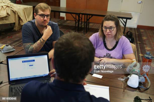Cole Geissinger and his wife Melissa Crain speak with Scott Triebel of Farmers Insurance about the next steps after losing their home in the Coffey...