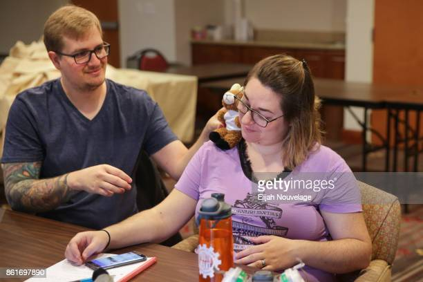 Cole Geissinger uses a stuffed animal to make his wife Melissa Crain smile during a meeting with Scott Triebel of Farmers Insurance to discuss the...