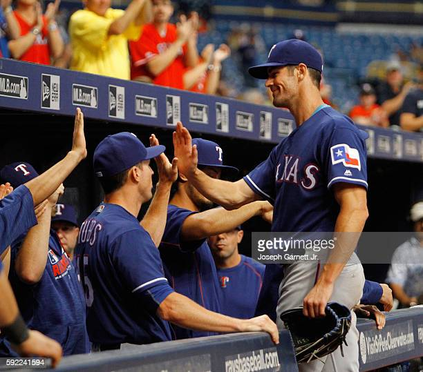 Cole Hamels 35 of the Texas Rangers celebrates with teammates after being pulled from the game in the eighth inning against the Tampa Bay Rays at...