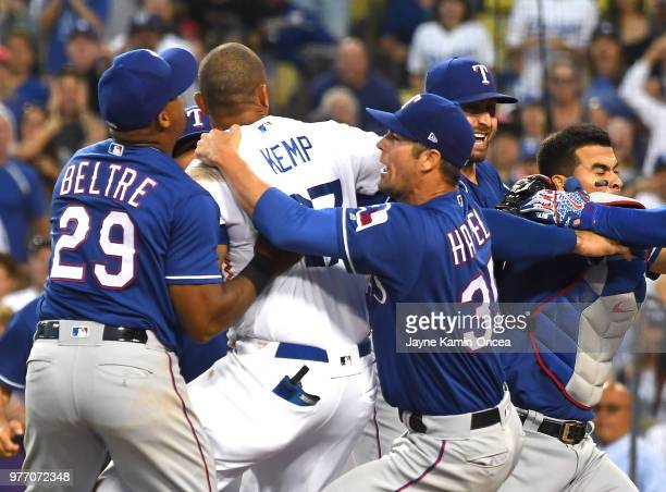 Cole Hamels and Adrian Beltre of the Texas Rangers try to hold back Matt Kemp of the Los Angeles Dodgers after a collision at home plate with...