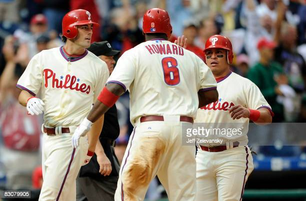 Cole Hamels and Carlos Ruiz are greeted by Ryan Howard of the Philadelphia Phillies after Hamels and Ruiz scored in the third inning of Game 1 of the...