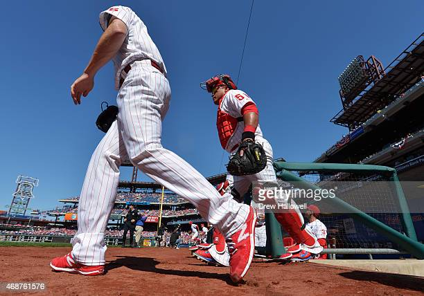 Cole Hamels and Carlos Ruiz of the Philadelphia Phillies walk onto the field before the game against the Boston Red Sox during Opening Day at...