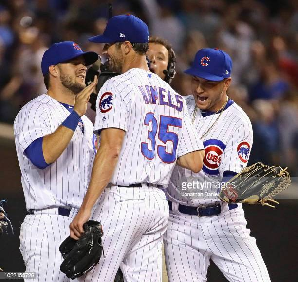 Cole Hamels of the Chicago Cubs is congratulated by David Bote and Albert Almora Jr#5 after a complete game win against the Cincinnati Reds at...