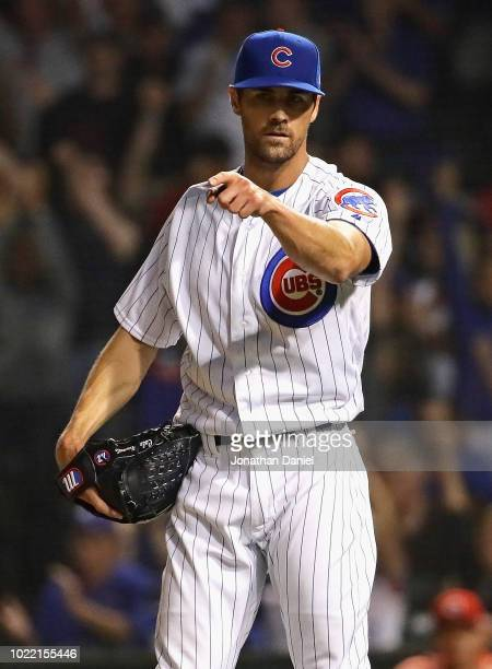 Cole Hamels of the Chicago Cubs points to third baseman David Bote after Bote started a double play to end the game against the Cincinnati Reds at...