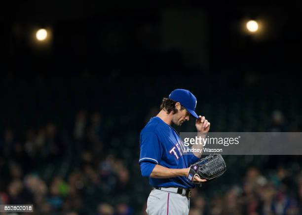 Cole Hamels of the Texas Rangers adjusts his hat as he prepares for a pitch against the Seattle Mariners at Safeco Field on September 21 2017 in...