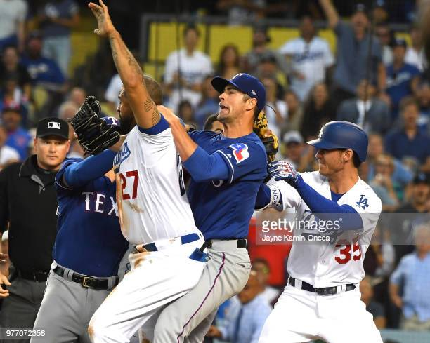 Cole Hamels of the Texas Rangers along with Cody Bellinger of the Los Angeles Dodgers try to hold back Matt Kemp of the Los Angeles Dodgers as...