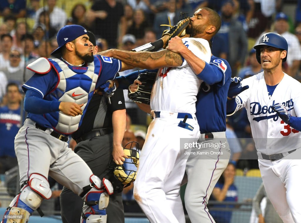 Cole Hamels #35 of the Texas Rangers and Cody Bellinger #35 of the Los Angeles Dodgers try to hold back Matt Kemp #27 of the Los Angeles Dodgers and Robinson Chirinos #61 of the Texas Rangers as tempers flared after a collision at home plate in the third inning at Dodger Stadium on June 13, 2018 in Los Angeles, California. A benches clearing brawl erupted with Kemp being ejected from the game.