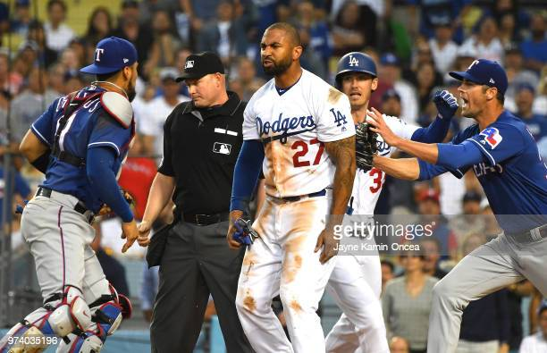 Cole Hamels of the Texas Rangers and Cody Bellinger of the Los Angeles Dodgers try to hold back Matt Kemp of the Los Angeles Dodgers and Robinson...