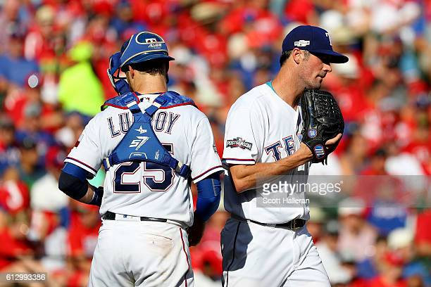 Cole Hamels of the Texas Rangers reacts with teammate Jonathan Lucroy on the mound against the Toronto Blue Jays during the third inning in game one...