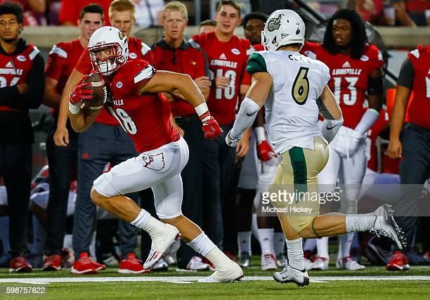 Cole Hikutini of the Louisville Cardinals runs the ball as Nick Cook of the Charlotte 49ers pursues at Papa John's Cardinal Stadium on September 1...