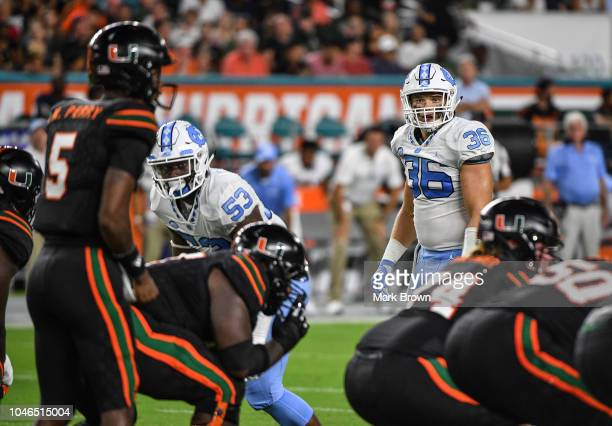 Cole Holcomb of the North Carolina Tar Heels lines up against the Miami Hurricanes at Hard Rock Stadium on September 27 2018 in Miami Florida