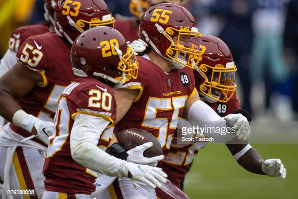 Cole Holcomb of the Washington Football Team celebrates with teammates after making an interception against the Dallas Cowboys during the first half...
