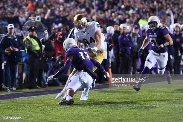 Cole Kmet of the Notre Dame Fighting Irish avoids a tackle by JR Pace of the Northwestern Wildcats during the first half of a game at Ryan Field on...
