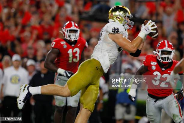 Cole Kmet of the Notre Dame Fighting Irish catches a second quarter touchdown in front of Monty Rice of the Georgia Bulldogs at Sanford Stadium on...