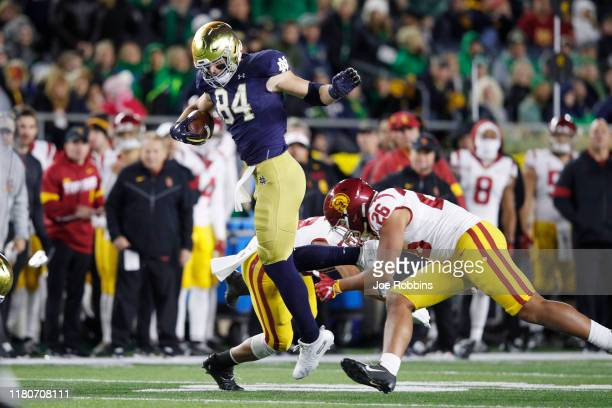 Cole Kmet of the Notre Dame Fighting Irish gets tripped up after catching a pass against Kana'i Mauga of the USC Trojans in the second half of the...