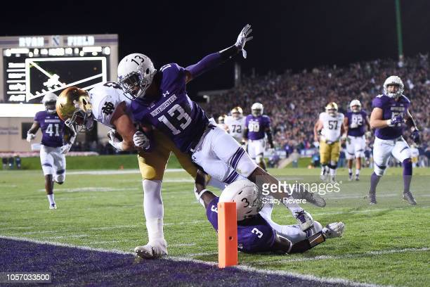 Cole Kmet of the Notre Dame Fighting Irish is knocked out of bounds by JR Pace and Trae Williams of the Northwestern Wildcats during the first half...