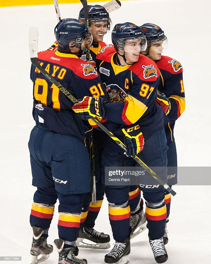 Cole Mayo #91, Connor McDavid #97, Dylan Strome #19 and Alex DeBrincat #12 of the Erie Otters celebrate a goal against the Windsor Spitfires on September 26, 2014 at the WFCU Centre in Windsor, Ontario, Canada.