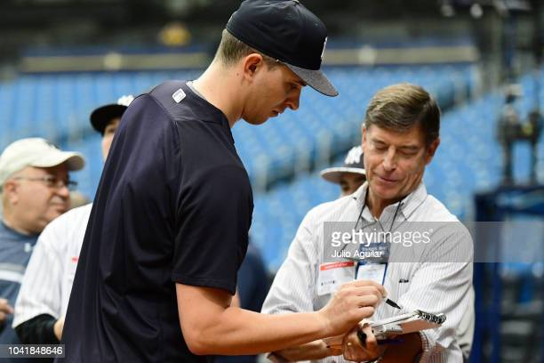 J Cole of the New York Yankees signs autographs for a fan before a game against the Tampa Bay Rays on September 27 2018 at Tropicana Field in St...