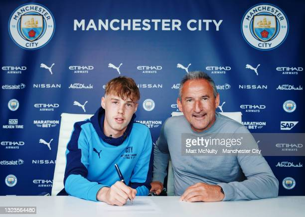 Cole Palmer of Manchester City signs a contract extension alongside Txiki Begiristrain, Director of Football at Etihad Campus on June 14, 2021 in...