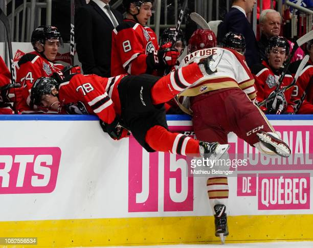 Cole Rafuse of the Acadie-Bathurst Titan hits Spencer Blackwell of the Quebec Remparts during their QMJHL hockey game at the Videotron Center on...