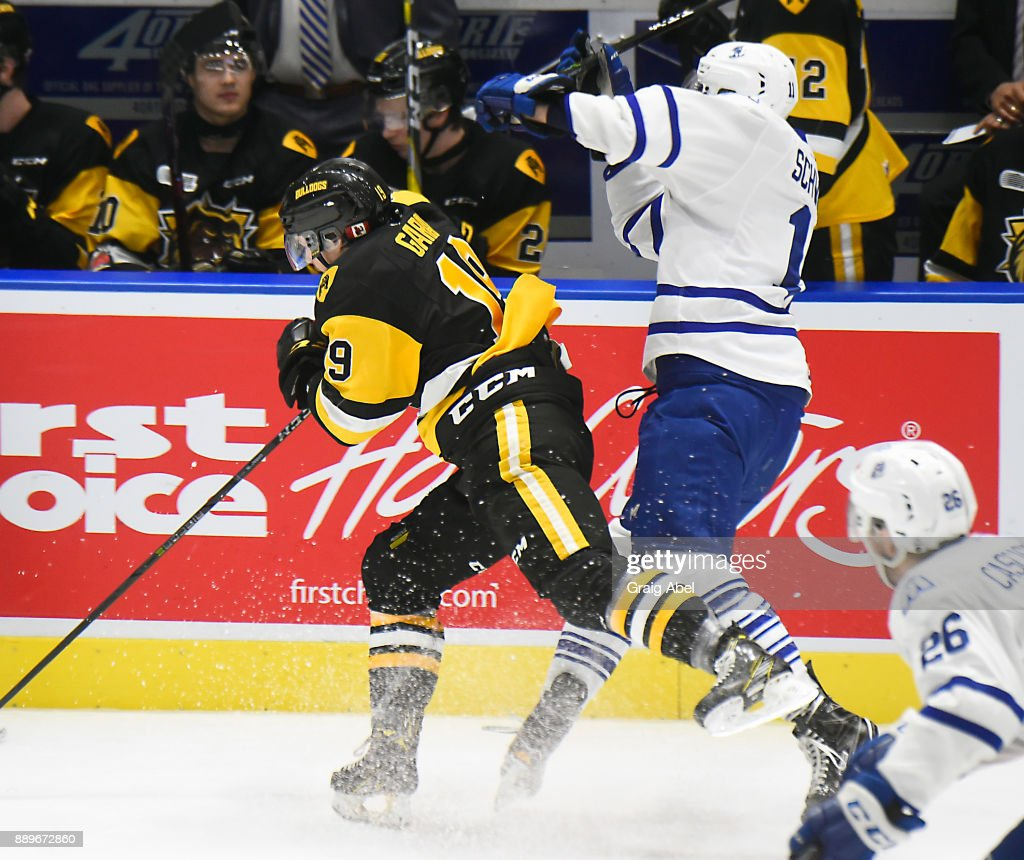 Cole Schwindt #11 of the Mississauga Steelheads takes a big hit by Ben Garagan #19 of the Hamilton Bulldogs during game action on December 10, 2017 at Hershey Centre in Mississauga, Ontario, Canada.