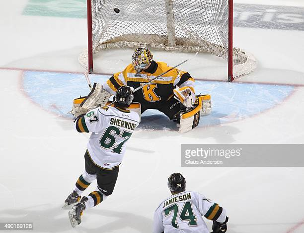 Cole Sherwood of the London Knights fores a shot past Jeremy Helvig of the Kingston Frontenacs during an OHL game at Budweiser Gardens on September...